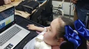 Uma adolescente em cadeira de rodas e aparelho respiratório, com um notebook a frente, na altura dos olhos