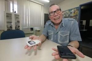 Foto de Gilson, um senhor de aparentemente 60 anos, com óculos e segurando um celular e um smartphone