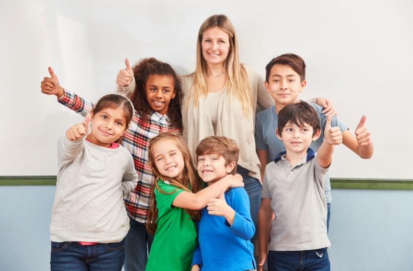 Grupo de alunos de diversas etnias com os dedos cruzados em torno de uma professora jovem