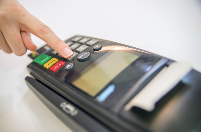 Foto de uma mão feminina teclando uma máquina de cartão.