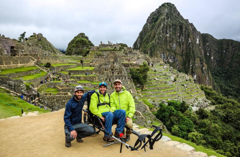 Foto em plano aberto com três amigos e a cidade dos incas ao fundo. Ao centro, está um homem em