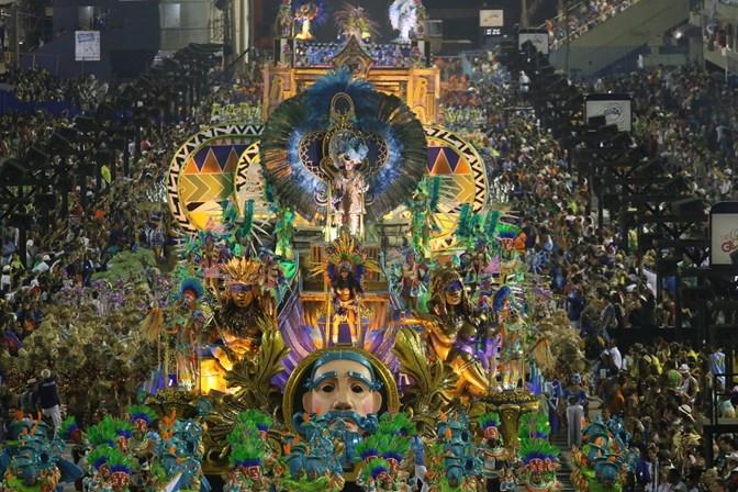 Foto do sambódromo durante o desfile de uma escola de samba com carros alegóricos e o público nas arquibancadas