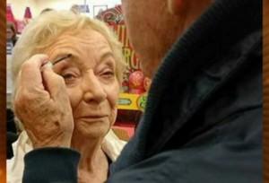 Um senhor de costas maquia os olhos de uma senhora de cabelos brancos