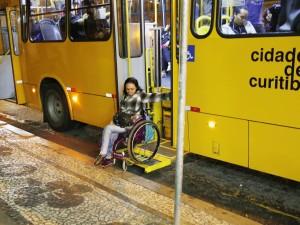 Mulher jovem na cadeira de rodas descendo de um ônibus.