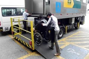 Foto de uma mulher empurrando um cadeirante em uma rampa de acesso em um aeroporto
