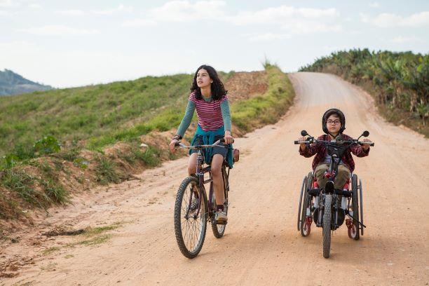 Cena do filme Sobre Rodas. Um garota e um garoto andam de bicicleta em uma estrada de terra. A bicicleta do garoto é adaptada