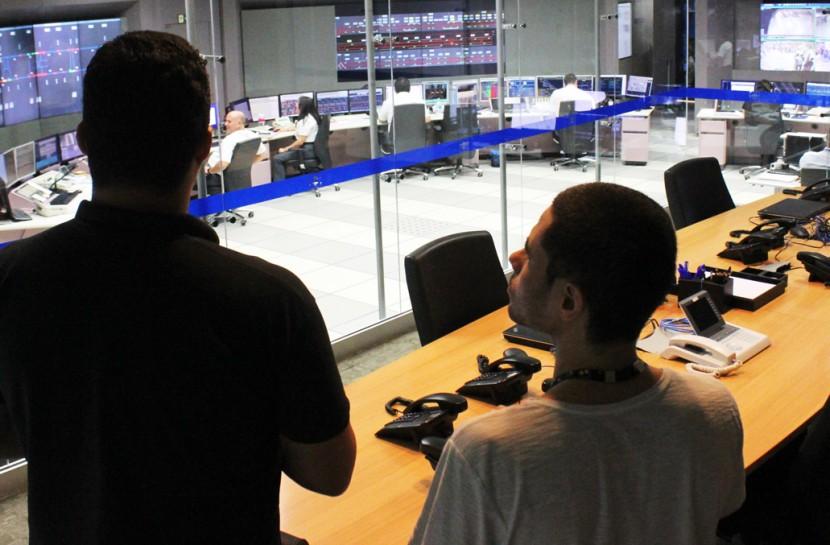 Foto de Lucas e um funcionário do metrô no Centro de Controle Operacional do Metrô, de costas, olhando através de uma parede de vidro para uma sala repleta de painéis eletrônicos e computadores