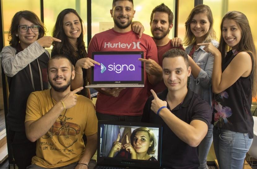 Foto de 4 homens e 4 mulheres em volta de um notebook, sorrindo e apontando para a tela, com logotipo da Signa