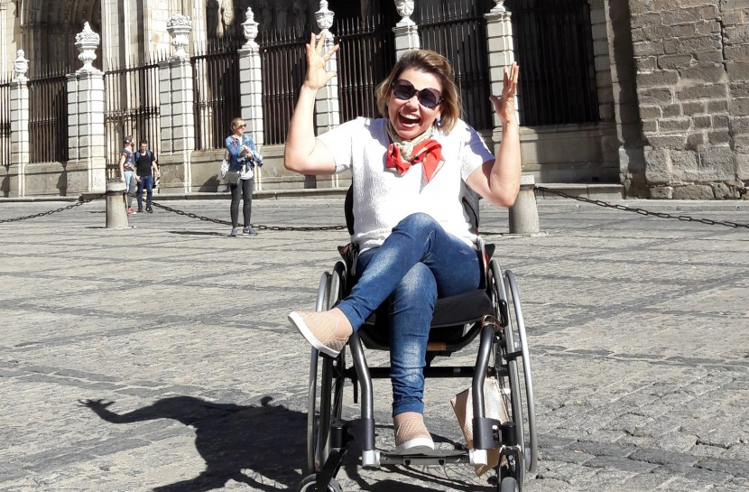 Foto da Laura Martins em frente à Catedral de Toledo, na Espanha. Ela está em uma cadeira de rodas e está com as mãos levantadas. Ela está sorrindo.