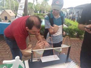 Foto do professor Eder Pires de Camargo mostrando um projeto de física para um aluno