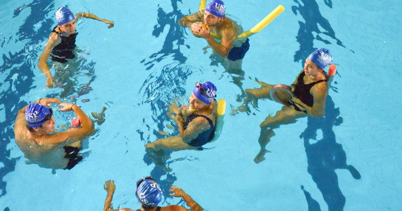 Foto em plano plongée dos alunos na piscina durante a aula