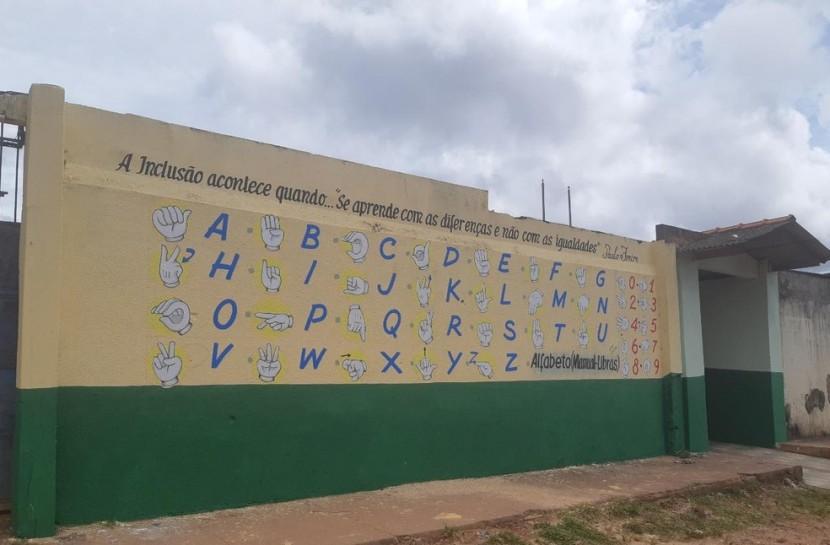 Foto da fachada da escola, com o alfabeto em Libras pintado no muro