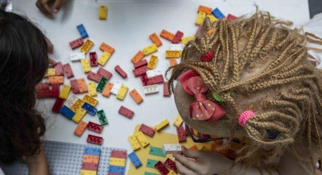 Foto de duas crianças, vistas de cima, brincando com peças do Lego Braile Bricks, em ambiente fechado.