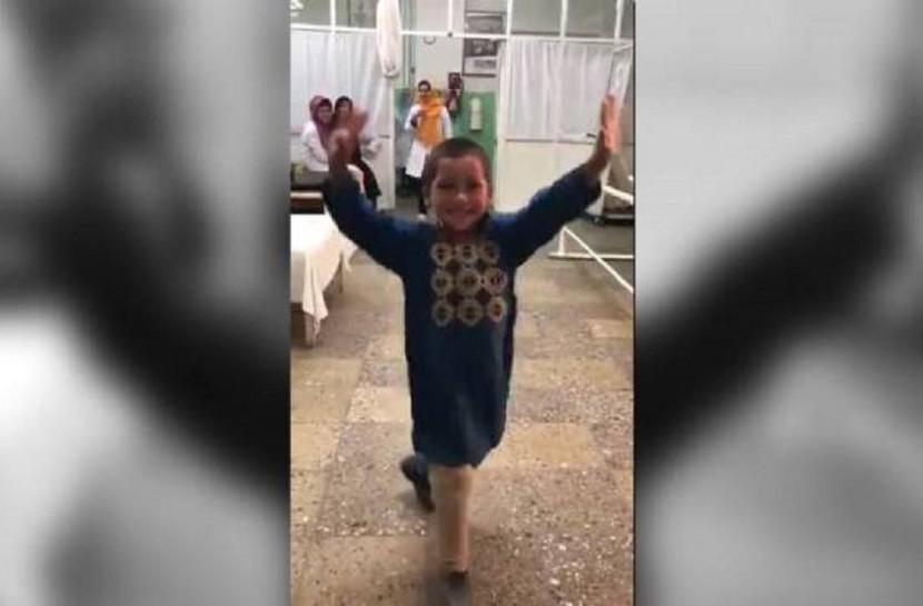 Frame do vídeo com o menino afegão sorrindo enquanto dança de braços erguidos