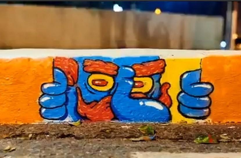 Plano detalhe do meio-fio com grafite de um homem abrindo espaços com as mãos, olhando para frente
