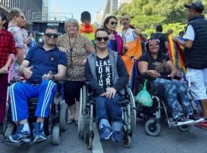 Foto de um grupo de dois homens e duas mulheres, sendo três deles cadeirantes, durante a parada. Eles sorriem na direção da câmera
