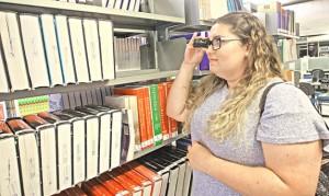 Foto de uma jovem estudante em uma biblioteca procurando livros em estantes com um óculos com lupa