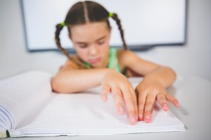 Foto de uma menina de aproximadamente 7 anos lendo em braile