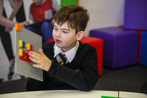 Um menino brincando com uma placa, onde se encontra peças de lego. O menino está vestindo uma blusa preta, uma camisa branca e uma gravata.