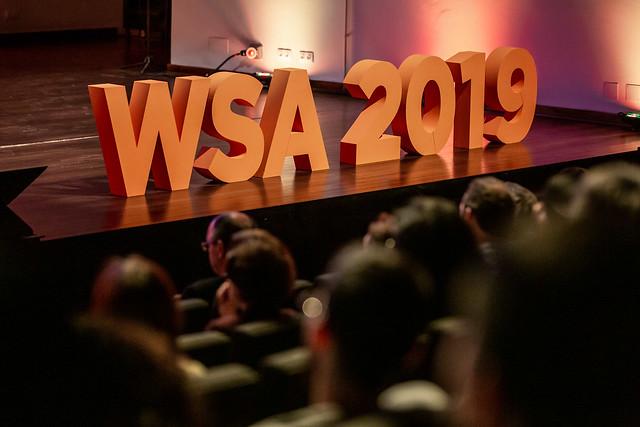Foto de um palco, com pessoas que assistem a uma palestra sentadas no auditório. No palco, em destaque, há a logo do Festival Global WSA na cor laranja.