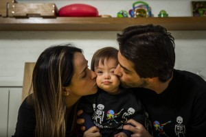 Foto da família Zylberstanj. No centro, o pequeno Pepo, entre a mãe, Marina e o pai, Henry. Ambos estão de rostos virados, beijando, ao mesmo tempo, as bochechas do filho.