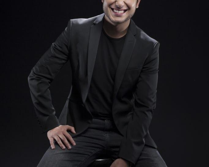 Foto em fundo preto de Alex Duarte sentado em um banco. Ele olha na direção da câmera e sorri. Ele possui cabelos e olhos escuros, está de barba e veste roupas da cor preta.