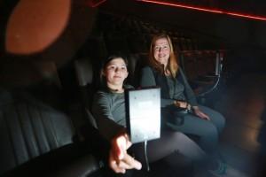 Foto de uma menina ao lado de uma mulher adulta em uma sala de cinema. As duas estão sentadas nas poltronas e sorrindo. A menina olha para uma pequena tela presa à poltrona.