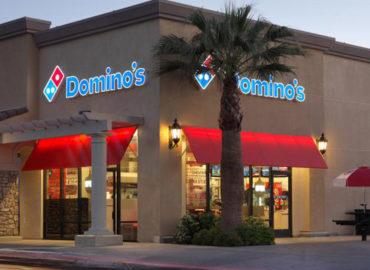 """Foto de uma das franquias da pizzaria. O estabelecimento tem suas paredes nas cores cinzas, acima das janelas há dourados vermelhos . Na parte superior do estabelecimento há letreiro escrito """"Domino's"""" com a imagem de uma peça de domino, logo da franquia."""