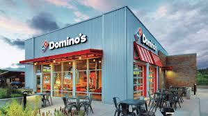 """Foto de uma das franquias da pizzaria Domino's. O estabelecimento tem suas paredes na cor cinza e acima das janelas há dourado vermelho. Na parte superior do estabelecimento há um letreiro escrito """"Domino's"""" com a imagem de uma peça de dominó, logo da franquia."""