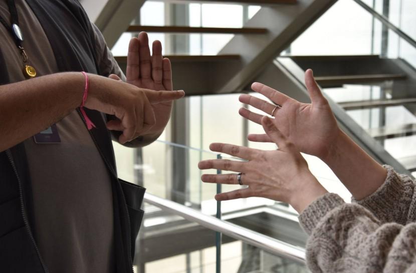 Foto de um homem fazendo o sinal do IMS Paulista em Libras e de uma mulher sinalizando língua de sinais em Libras.