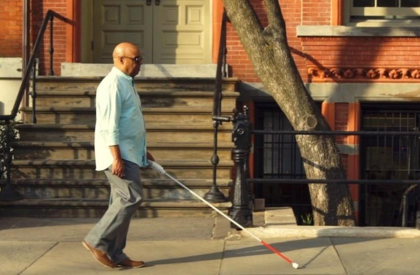 Foto de um homem negro caminhando com uma bengala branca