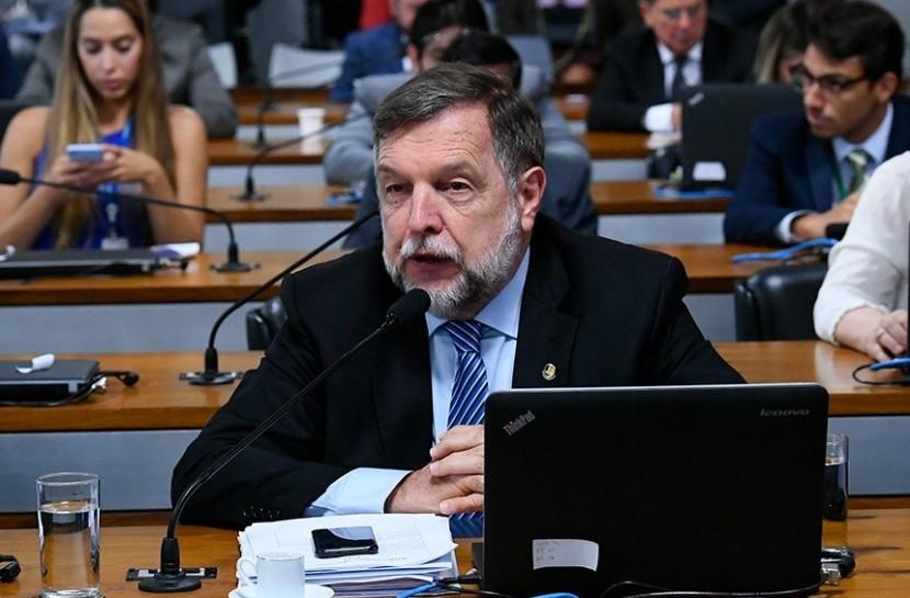 Foto do senador Flávio Arns sentado falando ao microfone com um notebook na sua frente.