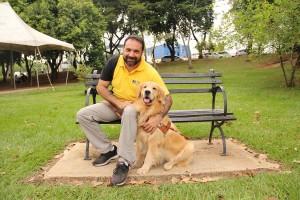 Foto de George Thomaz Harrison sentado em um banco e ao seu lado está um cão-guia da raça golden retriver