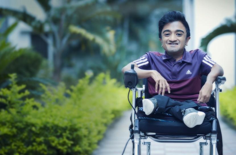 Foto de Jeevan em sua cadeira de rodas em uma calçada.