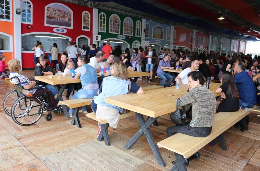 Foto de um grupo de pessoas, sendo uma delas cadeirante, sentadas à mesa em uma praça de alimentação