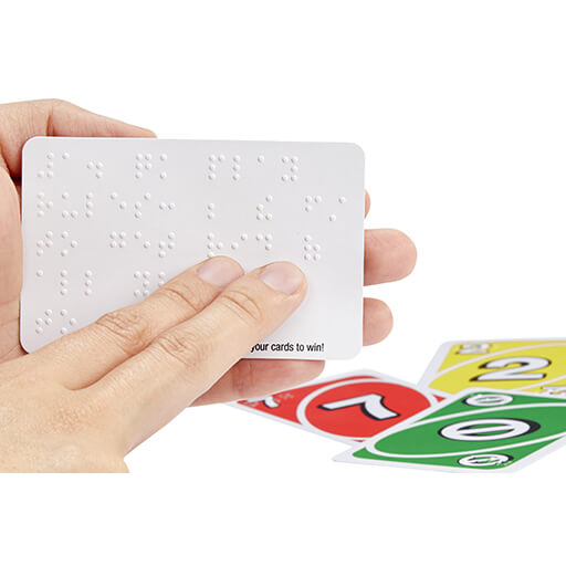 Foto da mão de uma pessoa segurando um cartão escrito em Braille. Ao fundo, há cartas coloridas em cima de uma superfície.