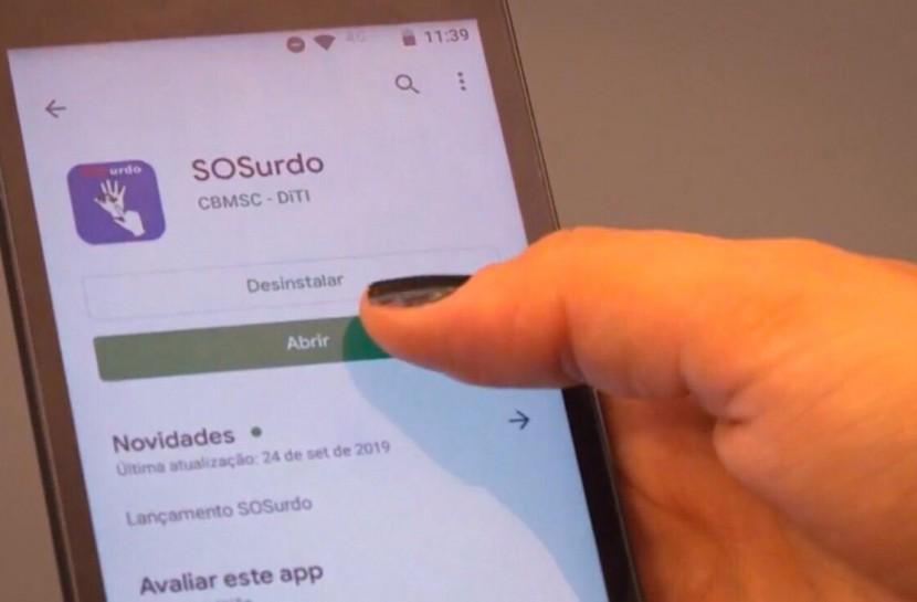 Foto de uma mão feminina segurando um smartphone. Na tela, aparece o aplicativo SOSurdo para download.