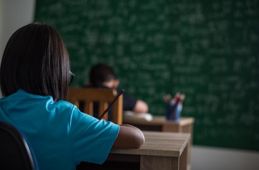 Foto de duas crianças sentadas em uma sala de aula.