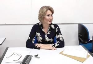 Foto de Jussara sentada com os braços cruzados em cima da mesa. Ela é branca, tem cabelo curto e loiro.