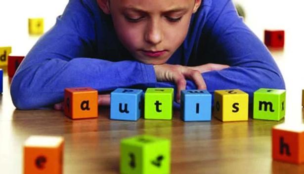 Foto de um menino olhando para blocos coloridos blocos com as letras a, u, t, i, s, m