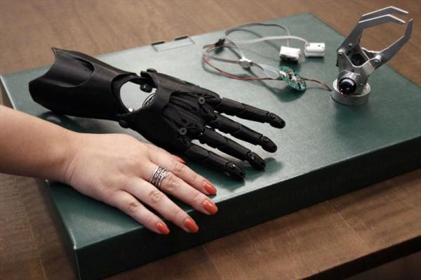 Foto de uma mão eletrônica, fios, uma garra e uma mão humana em cima de uma mesa.