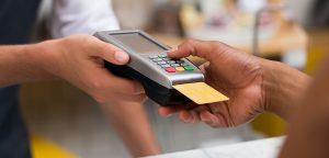 Foto em close de uma máquina de cartão de crédito sendo utilizada