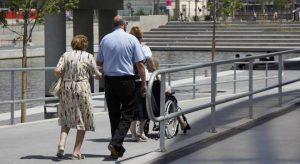 Foto de uma mulher conduzindo uma senhora cadeirante em uma calçada.