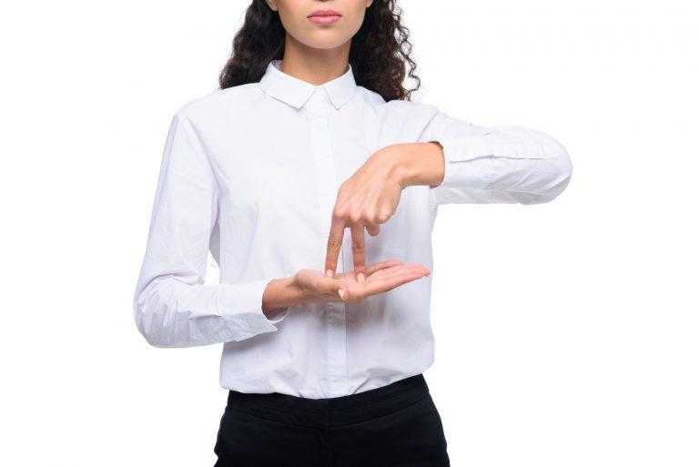 Foto de uma mulher em pé com o dedo indicador e médios da mão esquerda em cima da mão direita com a palma estendida.