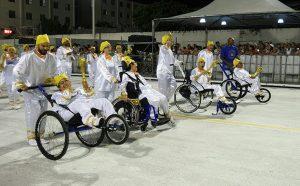 Foto de um grupo de pessoas fantasiadas, sendo que alguns são cadeirantes e estão sendo conduzidos por outras pessoas