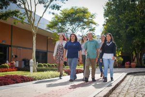 Foto de cinco mulheres e um homem com uma bengala caminhando juntos