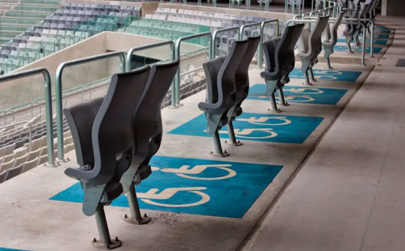 Foto parcial de uma arquibancada de estádio, com poltronas dobráveis e espaços com o símbolo de identificação da pessoa com deficiência, em branco e azul, pintados no chão