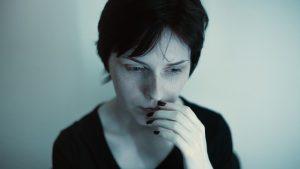 Foto de uma mulher com expressão assustada com a mão a boca