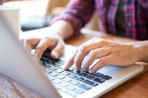 Foto em close de mãos digitando em um laptop