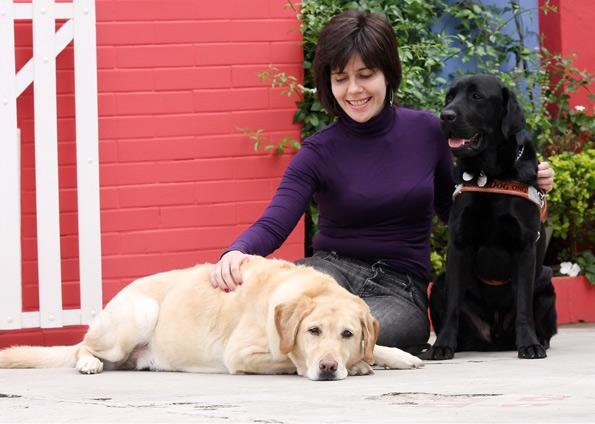 mulher sentada com dois cães-guia